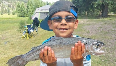 Isaiah Chavez, 7, of Santa Fe, caught this 17-inch rainbow trout July 9 using a brook trout colored Panther Martin.