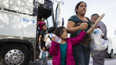 Migrants get off a bus after being released by ICE near a Greyhound bus station in Phoenix June 2, 2014.
