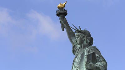 The Statue of Liberty stands against a clear sky