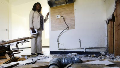 Melinda Dawkins, with the Montgomery Housing Authority, looks at the damage vandals inflicted on the apartment Rosa Parks lived in when she sparked the Montgomery Bus Boycott. The thieves tore out walls to take copper from the home