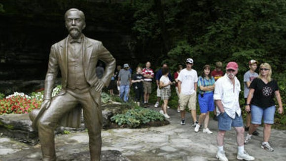 Visitors file past a statue of Jack Daniel, the original one, at the firm's Lynchburg distillery. (File Photo)