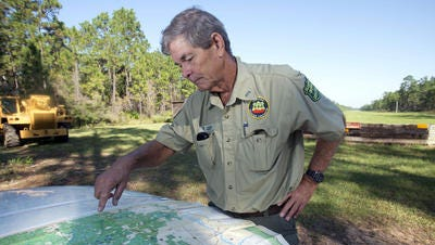 Blackwater State Forest Manager Tom Ledew maps out areas of the Munson area forest being considered by the military for training exercises beginning sometime in 2014.