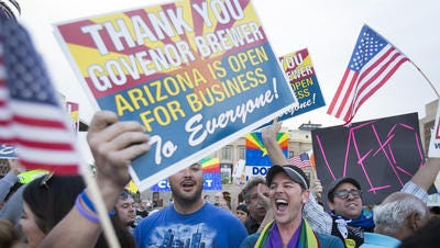 Protestors, including Christopher Bullock, center, celebrate after hearing that Arizona Gov. Jan Brewer was going to veto the controversial SB 1062.