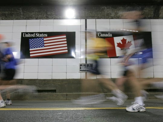Runners breeze past the international border from Canada