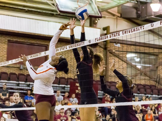 Freshman middle blocker Taryn Knuth (13) locks down Virginia Tech's offense and blocks the ball.