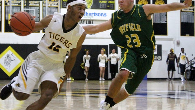 Jared Session, left, drives past Nick Flores on Tuesday night at the Tiger Pit.