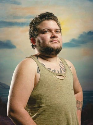 """""""Rowboat on the Beach (Tash)"""" by Lorenzo Triburgo is part of """"Transportraits,"""" a series of unlikely heroic portraits of transgender men against a created environment. It is on exhibit through March 10 at the Fairbanks Gallery at Oregon State University."""