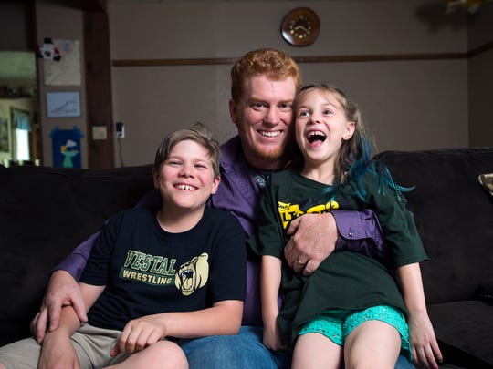 Lance Brown with his son Drake 11, and his daughter Davia, 7, inside their Vestal home.