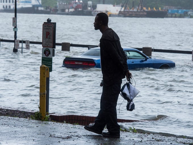 Jermaine Brown walks past a submerged vehicle as the