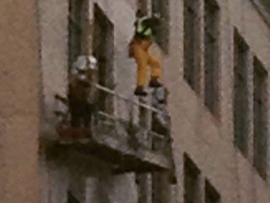 A window washer is shown dangling from the eighth story of the Bank of America building in Wilmington. He was later safely rescued.