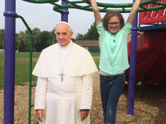 A student at St. Theresa Catholic School poses with a life-sized cutout of Pope Francis.