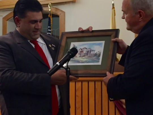 "Toms River Councilman John ""Sevas"" Sevastakis admires a Virginia Perle painting of town hall, presented to him by his council colleagues, including Councilman Maurice B. ""Mo"" Hill Jr."