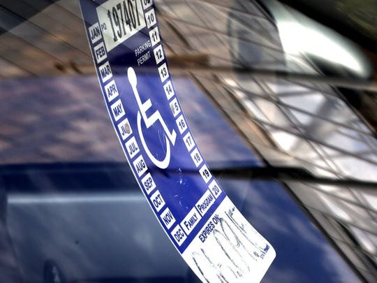 In this file photo, a parking tag for people with disabilities hangs from the rearview mirror of a car at a metered parking spot in Portland, Oregon.