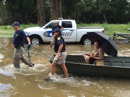 Caddo Sheriff's Reserve Deputy Cecil Windham, Lt. Donna Jackson, and Cpl. Frank Edmondson transport a Baton Rouge resident to safety after successfully evacuating her from her home.