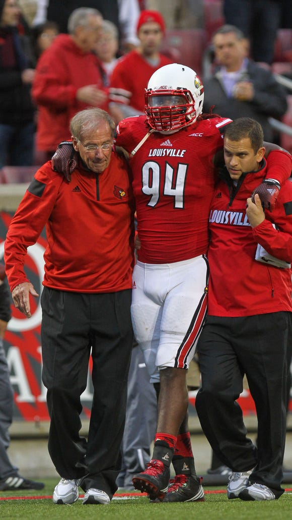 Louisville's Lorenzo Mauldin is helped off the field after being injured in the game against NC State Saturday. Oct. 18, 2014