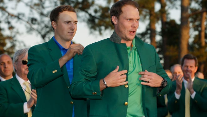 Danny Willett is helped into the green jacket by Jordan Spieth after Willett won the 2016 The Masters golf tournament at Augusta National Golf Club.