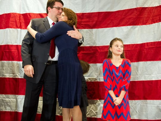 Eddie Smith kisses his wife, Lana, after defeating incumbent Gloria Johnson for the state House District 13 seat on Nov. 4, 2014. At right is their daughter Lauren Smith.