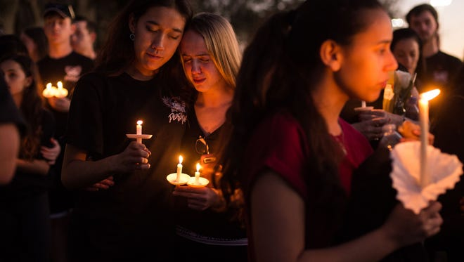 Members of the Stoneman Douglas Eagle Regiment mourn among thousands of other community members during a candlelight vigil at the Pine Trails Park amphitheater Thursday, Feb. 15, 2018, a day after the mass shooting at Marjory Stoneman Douglas High School in Parkland.