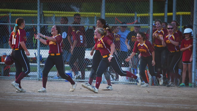 Roosevelt softball players run toward their teammate Shayla Running after the last run in the game against O'Gorman Thursday at Sherman Park.