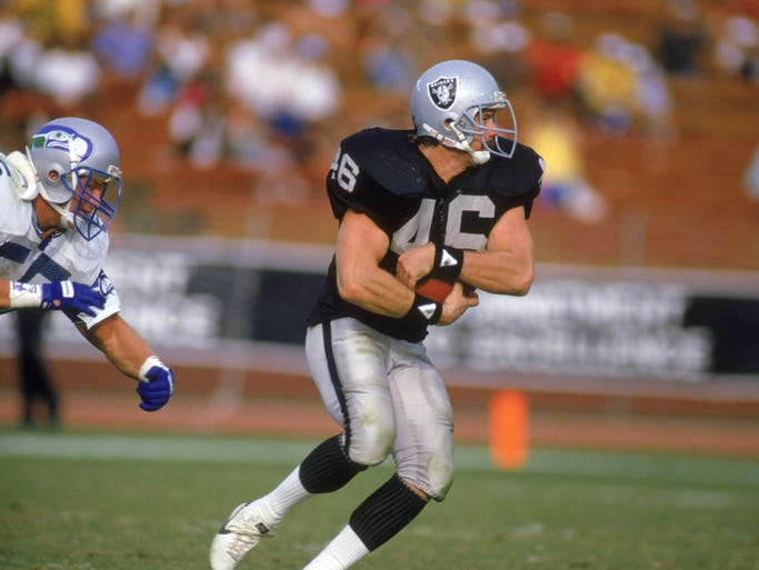 Todd Christensen of the Los Angeles Raiders carries the ball during a 1980s game against the Seattle Seahawks at Memorial Coliseum in Los Angeles, California. Christensen passed away on November 13, 2013 at the age of 57.
