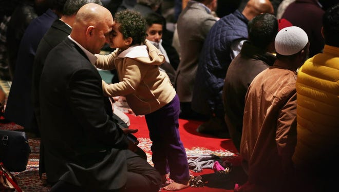 Sona Agha, 2, of Burke, Va., shares a moment with her father, Agha Hasnain, during prayer Nov. 14, 2014, at the National Cathedral in Washington.