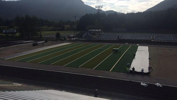 Workers can be seen laying down a new artificial turf field inside Reynolds' Dalton Stadium on Thursday.