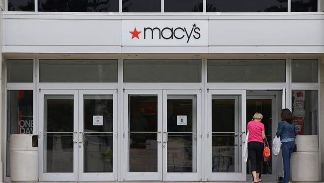 In this July 10, 2015, photo, shoppers walk into a Macy's department store at the Hanover Mall in Hanover, Mass.