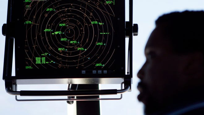An traffic controller stands Sept. 18, 2008, beneath a radar screen in the control tower at Washington's Reagan National Airport.