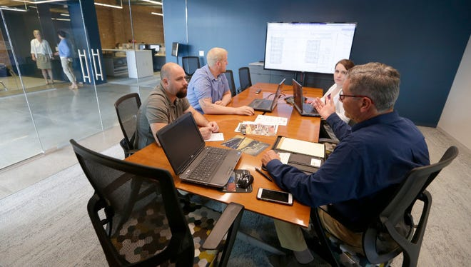 Employees work in a conference room in Bray Architects' new offices, at 829 S. 1st St., a former Walker's Point industrial building that was renovated.