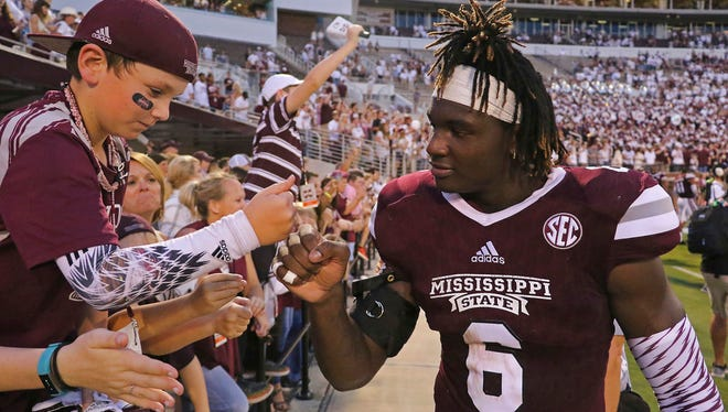Mississippi State linebacker Willie Gay Jr. (6) does a fist-bump with 9-year-old Trip Lefoe of Nesbit.