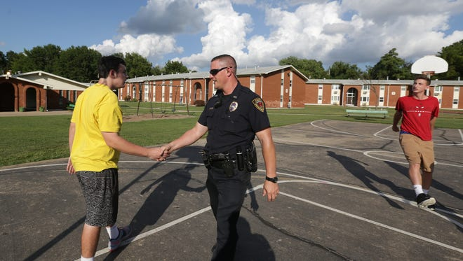 In this file photo, Springfield police officer Kevin Grundy plays a quick game of basketball with residents of the John B. Hughes neighborhood. He shakes hands with A.J. Blakey after the game. Grundy said games like this often happened during his foot patrols.