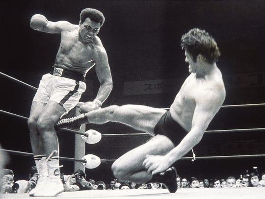 5 Jul 1976:  Muhammad Ali fends off a kick from wrestler