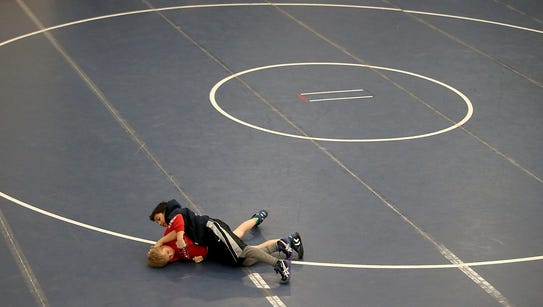 Youngsters grapple on the mat in between rounds during