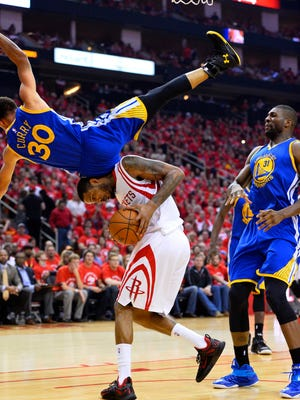 Warriors guard Stephen Curry (30) falls over Rockets forward Trevor Ariza during the first half of Game 4 of the Western Conference finals at the Toyota Center in Houston.