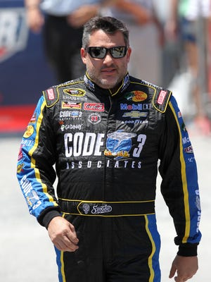 Tony Stewart walks on the grid prior to the Sprint Cup race at Dover International Speedway on May 31.