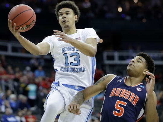 In this March 29 file photo, North Carolina's Cameron Johnson (13) heads to the basket past Auburn's Chuma Okeke (5) during the first half of an NCAA Midwest Regional semifinal game in Kansas City, Mo.