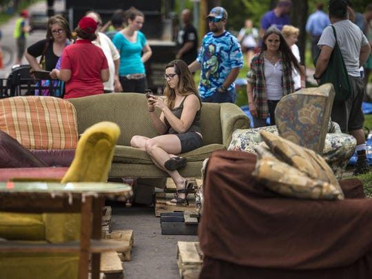 Stephanie Kokes texts her roommate after finding a couch during the Student Move Out Project on Loomis Street in Burlington on Wednesday, May 25, 2016.