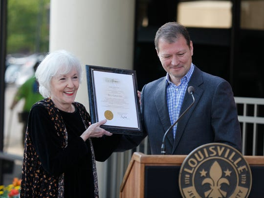 Author Sue Grafton holds up a plaque given to her by Chris Poynter, of the Mayor's Office, in April 2016.