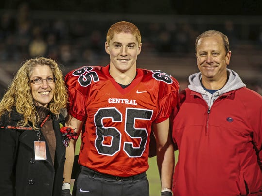 "This Oct. 31, 2014, photo provided by Patrick Carns shows Timothy Piazza, center, with his parents Evelyn Piazza, left, and James Piazza, right, during Hunterdon Central Regional High School football's ""Senior Night"" at the high school's stadium in Flemington, N.J. Prosecutors in Pennsylvania are set to announce, Friday, May 5, 2017, the results of a grand jury investigation into the death of the Penn State student, Timothy Piazza, who fell down steps Feb. 4, during an alcohol-fueled pledge ceremony. (Patrick Carns via AP)"