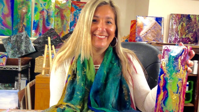 In her art-filled studio, Franklin artist Jacqueline Drake wears fabric embellished with her special design. These designs will be used for yoga pants, capris and tank tops.