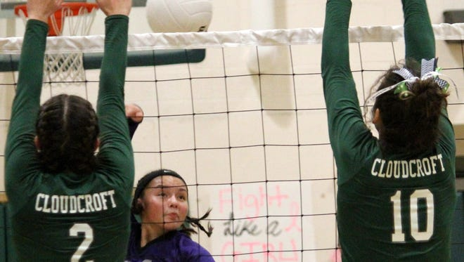 Mescalero's Alyn Kazhe-Kirgan, center, spikes a ball in between Cloudcroft's Ella Puckett (2) and Laci Toddy (10) on  Thursday night at Cloudcroft High School.