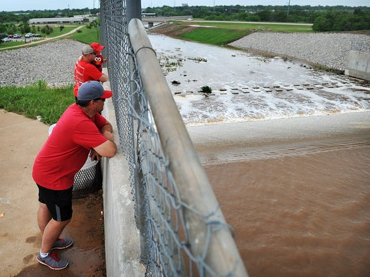 TORIN HALSEY/TIMES RECORD NEWS File Photo  Sean Sullivan, Michael Poirot and his son, Madix Poirot, stopped by the Lake Wichita spillway like many others in 2015, to see water going over the spillway, something that had not happened in several years due to the exceptional drought the North Texas area is experiencing. A rainy Wednesday marks four years since the lakes reached 100 percent for first time since the drought began.