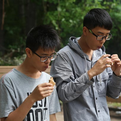 Zhang Le Tao, left, and Wu Siyuan eat s'mores at the