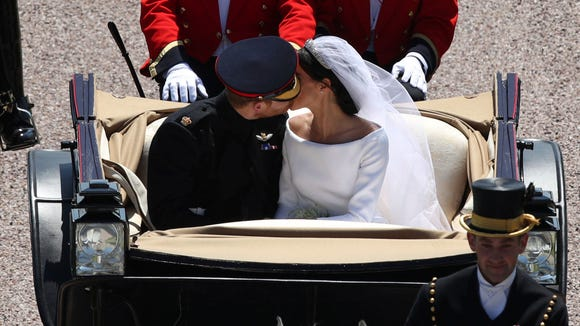 Prince Harry and Duchess Meghan kiss as they ride in