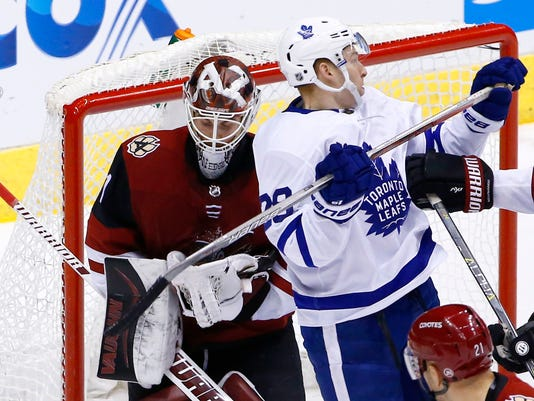 Arizona Coyotes goalie Scott Wedgewood, left, makes a save on a shot behind Toronto Maple Leafs right wing Connor Brown (28) during the third period of an NHL hockey game Thursday, Dec. 28, 2017, in Glendale, Ariz. The Maple Leafs defeated the Coyotes 7-4. (AP Photo/Ross D. Franklin)