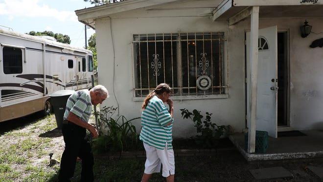 Long-time Fort Myers resident Ralph Hauser, 92, and his wife, Jackie, 88, walk back to their home after sitting for a portrait for The News-Press on Thursday. Code enforcement  has ordered them to fix their roof, get rid of the tarp or face comdemnation.