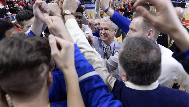 Irondequoit head coach Chris Cardon, center, huddles with his team after their win in the NYSPHSAA Boys Basketball Championships Class A semifinal.