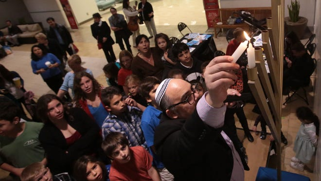 Rabbi Andrew Bentley of Temple Sinai lights the first candle on the menorah on the first day of Hanukkah in 2014.