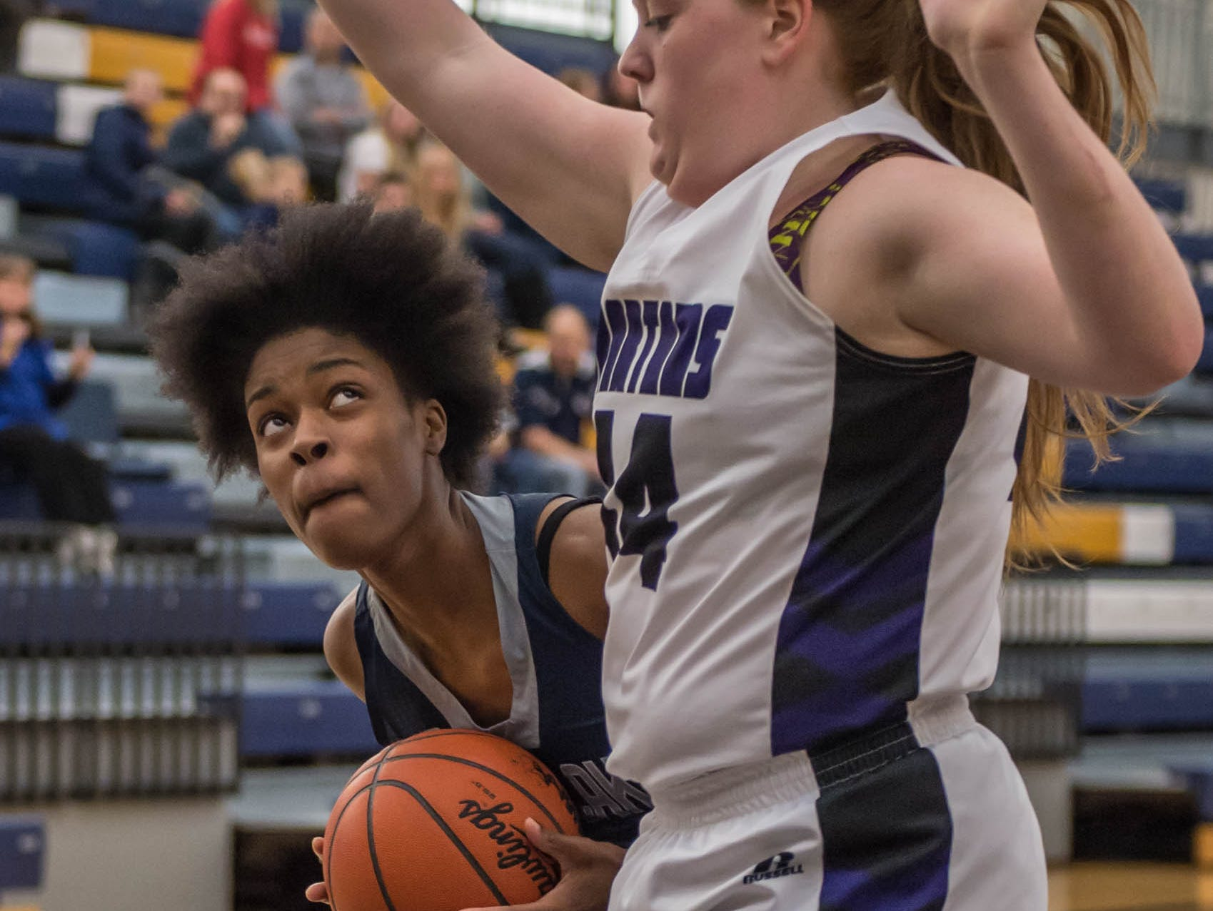 Gull Lake's Imani Morrow (44) looks to the basket while being guarded by Lakeview's Emily Eldridge (44) during district game Wednesday evening.
