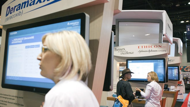 Representatives for Novartis present information at the  American Veterinary Medical Association's annual convention at McCormick Place in Chicago in July 2013. Any veterinarian who listened to the information about eight different drugs offered by the company could receive a free portable speaker.